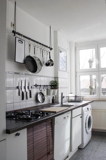 A small white kitchen with black countertops. There is a set of hooks with pans and other kitchen tools hung from them.