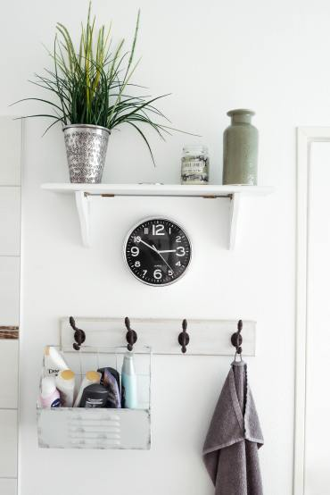 A white wall in a bathroom. On this wall is a shelf, a clock, and four hooks with bathroom essentials hung on them.