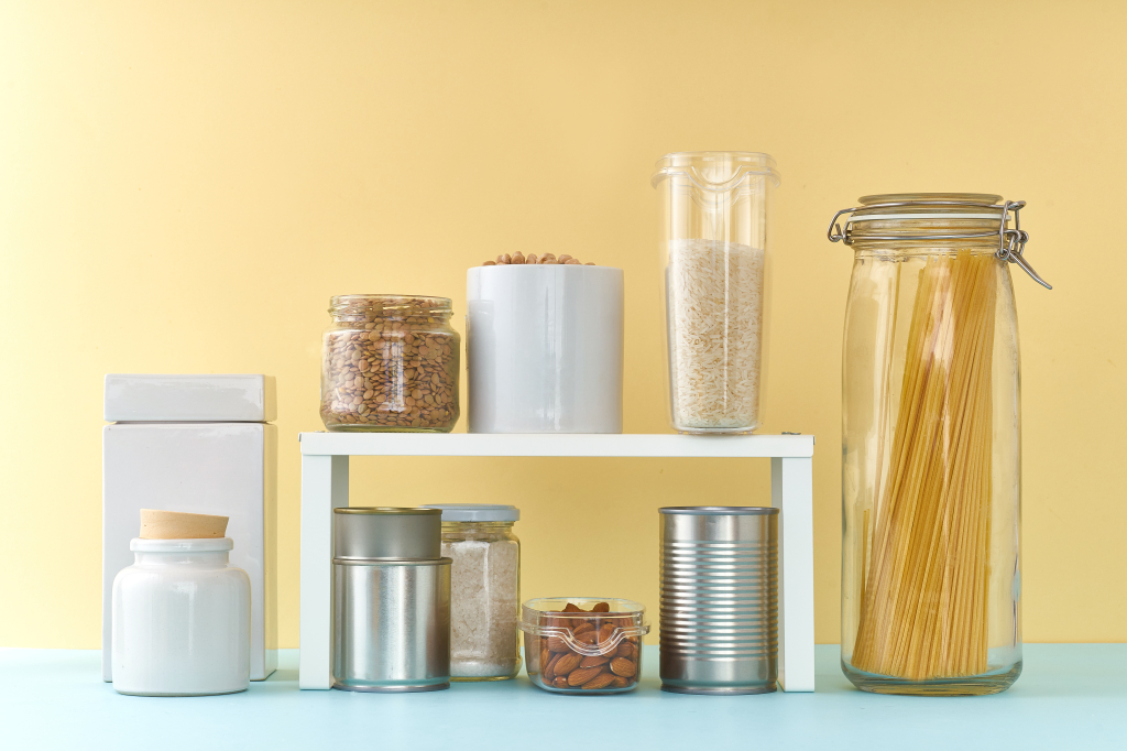 Pantry items on a light blue counter with a yellow wall behind. These items are demonstrating the use of a shelf organizer.