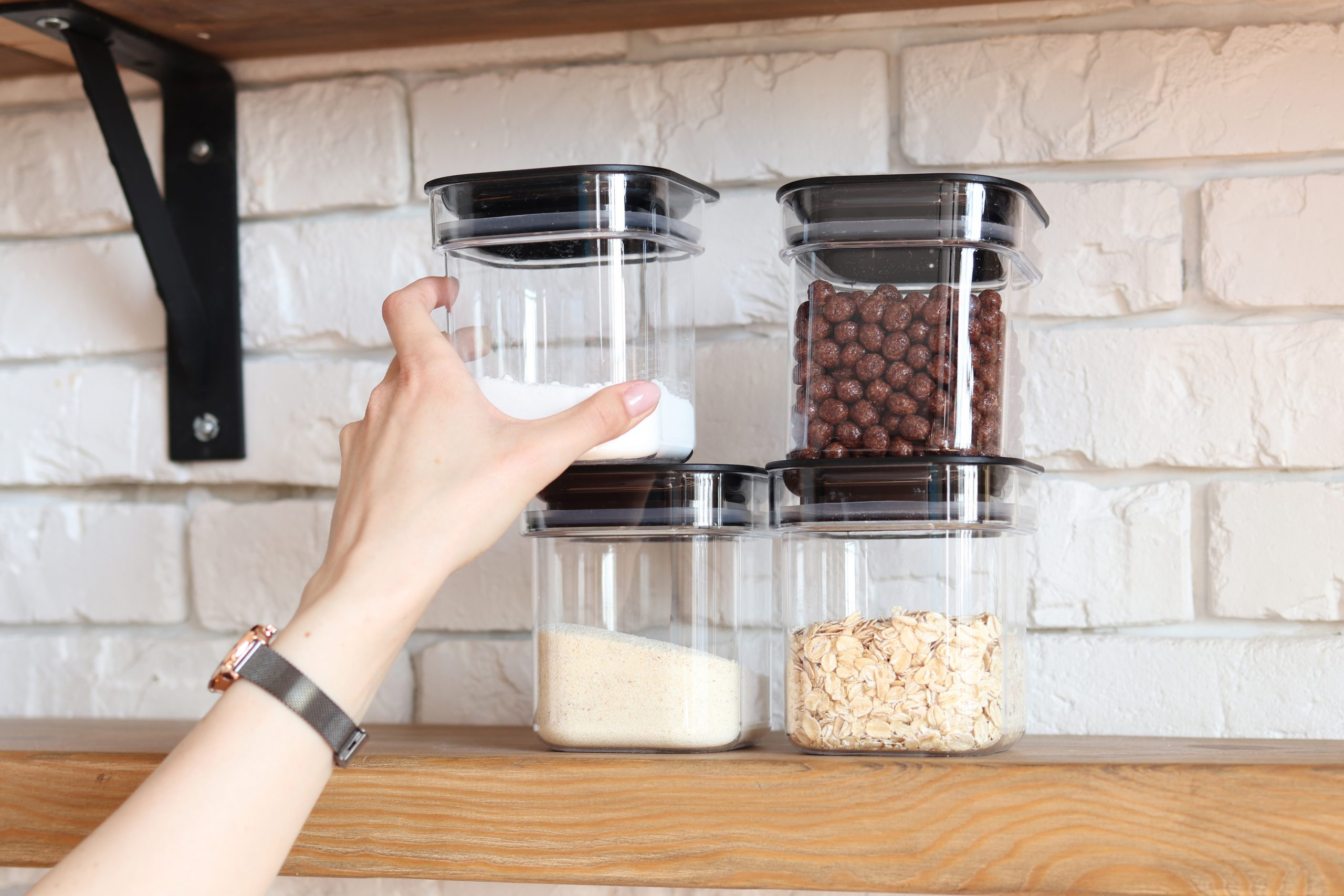 A hand reaching up to grab a small storage container off a shelf. There are four containers stacked on the shelf.